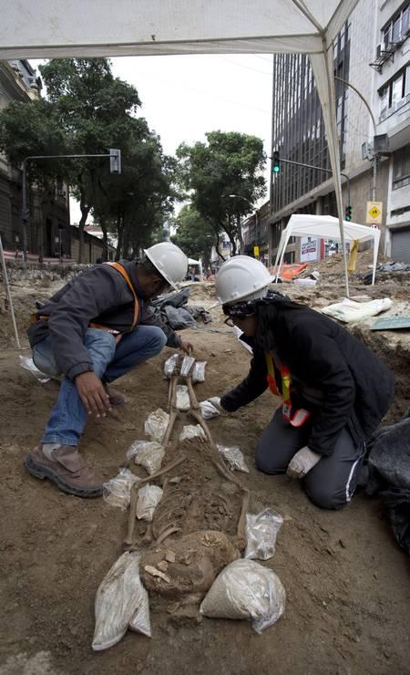 Arqueólogos com ossada encontrada no Centro Foto: Márcia Foletto / Agência O Globo