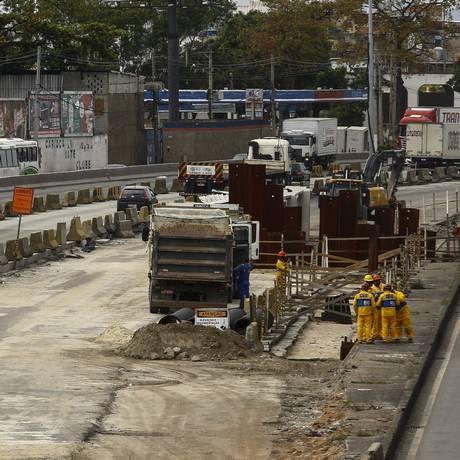 Grupo pequeno de operários trabalha na pista Foto: Uanderson Fernandes / Agência O Globo