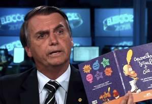 Em entrevistsa ao Jornal Nacional, Bolsonaro mostra o livro 'Aparelho sexual e cia' Foto: Reprodução / TV Globo