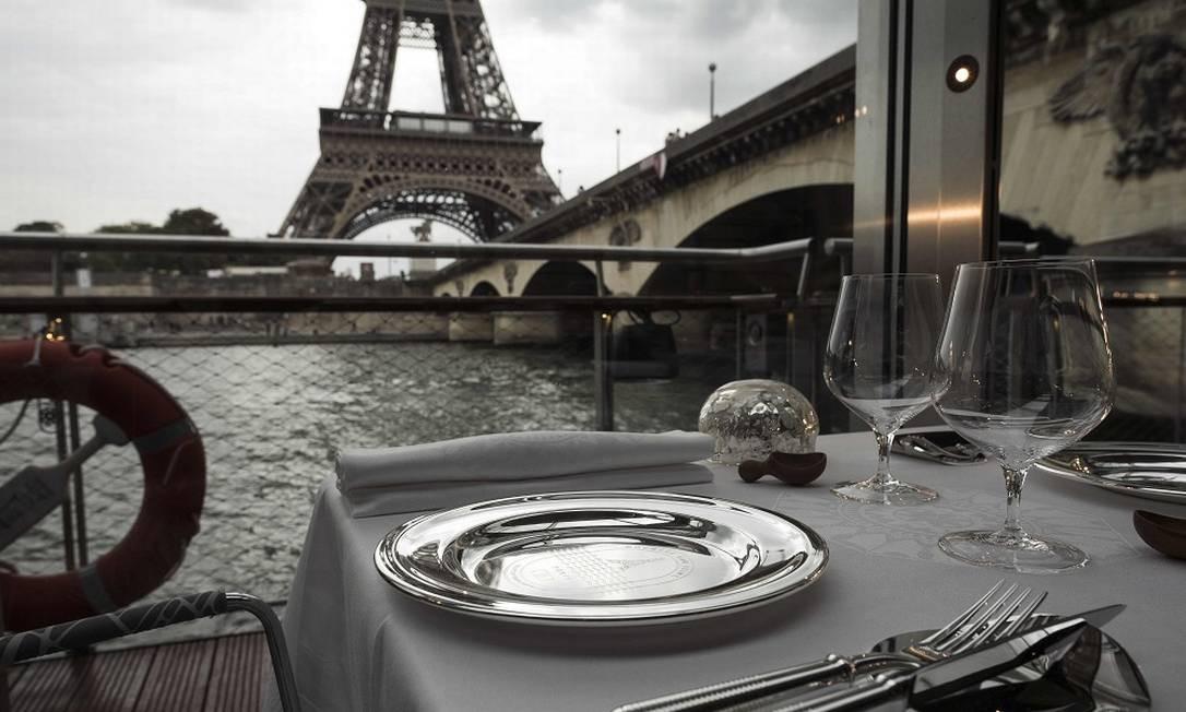 """Vista de uma das mesas do """"Ducasse sur Seine"""", atualmente atracado. A embarcação vai fazer um passeio de cerca de 1h30 no almoço e outro, pelo mesmo período, no jantar LIONEL BONAVENTURE / AFP"""