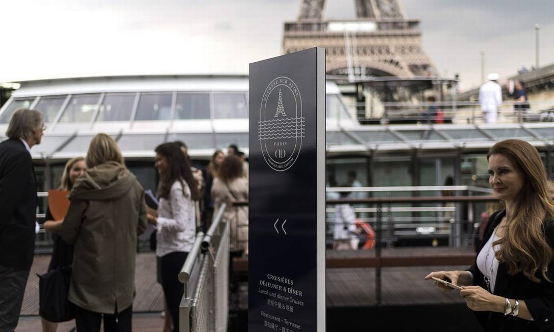 Pessoas observam a entrada do barco elétrico que servirá até 130 pessoas. O almoço começa em 100 euros e o jantar em 150 LIONEL BONAVENTURE / AFP