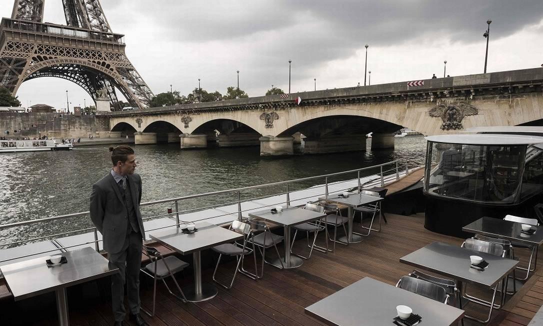 """Garçom observa as mesas do """"Ducasse sur Seine"""", do chef Alain Ducasse, que tem 21 estrelas do Michelin LIONEL BONAVENTURE / AFP"""