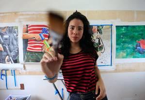 Cibelle Arcanjo brinca com a câmera durante a foto em seu ateliê na Babel 08, em Icaraí, com alguns de seus trabalhos ao fundo Foto: r / Agência O Globo