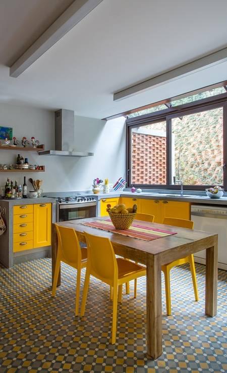 Um projeto de cozinha em casa de campo. O espaço recebeu teto em vidro para captar maior claridade. A mesa em madeira no centro serve de apoio para cozinhar. Os armários em amarelo combinam com as cores do piso em ladrilho hidráulico. Foto: Andre Nazareth / Divulgação