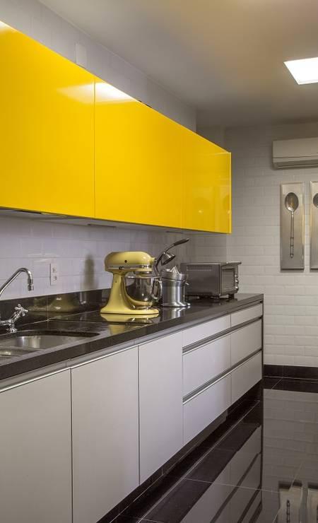 A copa/cozinha tem portas de correr que, quando abertas, integram o ambiente à sala de jantar. Na cozinha do dia a dia foi usado o mesmo tem de amarelo da cozinha gourmet. Foto: Divulgação / Divulgação
