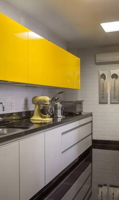 A copa/cozinha tem portas de correr que, quando abertas, integram o ambiente à sala de jantar. Na cozinha do dia a dia foi usado o mesmo tem de amarelo da cozinha gourmet. Divulgação / Divulgação