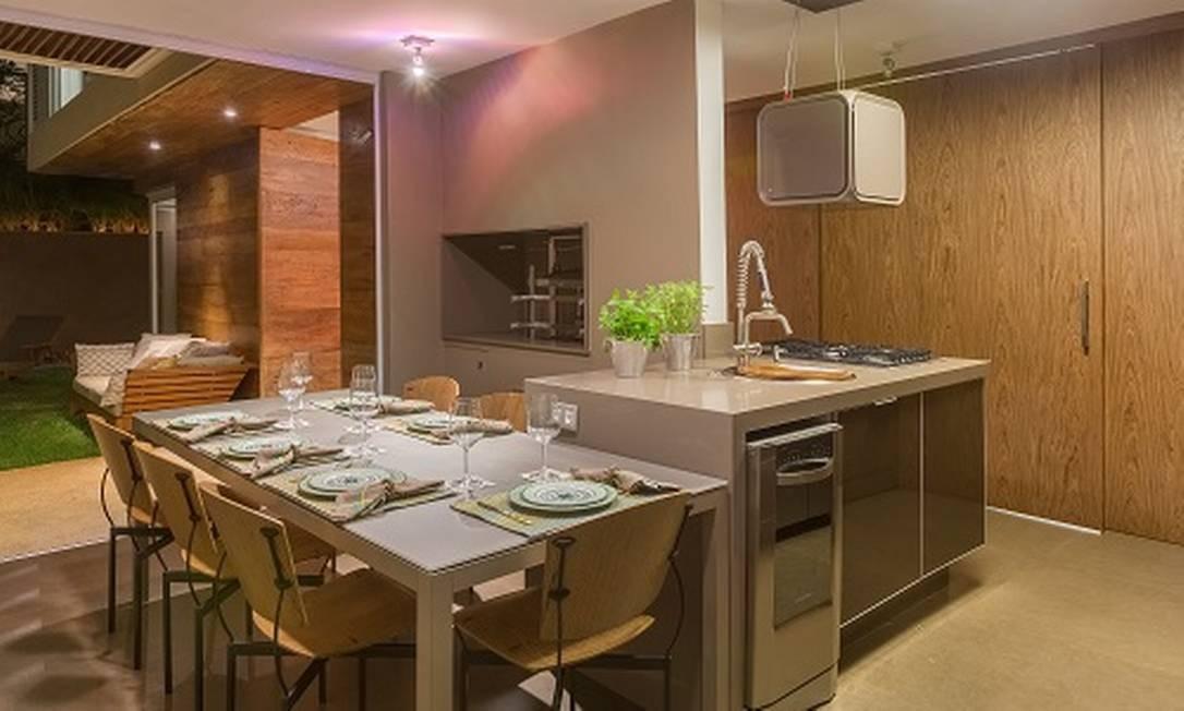 Nesta cozinha gourmet, localizada em uma casa, se integra totalmente à área de lazer. Andrea Chicharo embutiu uma churrasqueira, a mesa fica encostada à bancada da cozinha. A ambientação é toda em madeira e tons neutros nos vidros dos armários. Foto: Divulgação / Divulgação