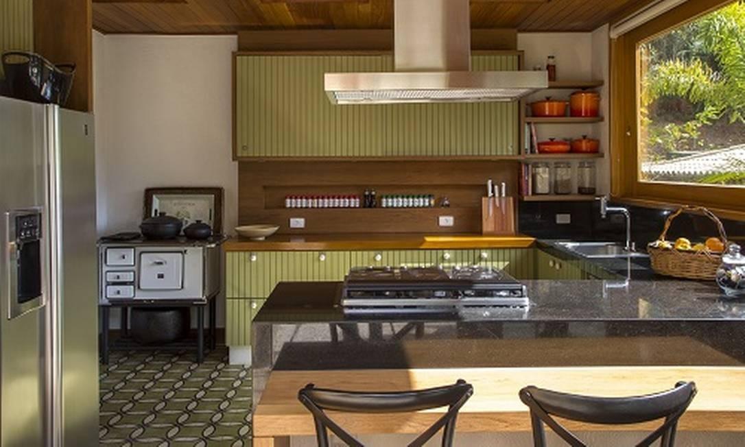 Essa é uma cozinha de casa de campo. O objetivo foi projetar um espaço com elementos rústicos e aconchegante. Piso em ladrilho hidráulico, teto em lambri e armários feitos sob medida para o local, com partes pintadas e nicho em madeira para temperos. Divulgação / Divulgação