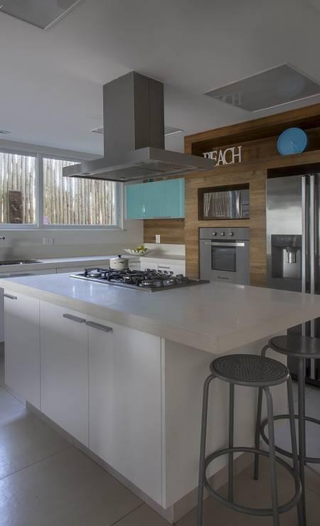 Esta cozinha em casa de praia recebeu uma ilha com cooktop e bancada vantajosa para trabalhar. Os móveis brancos, com o armário superior em azul turquesa, deixaram o espaço descontraído e moderno. O painel em madeira de demolição deu charme e aconchego especial. Foto: Divulgação / Divulgação