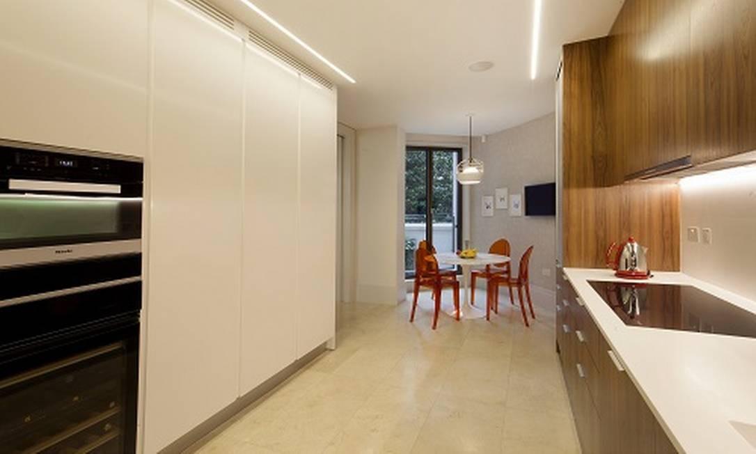Num estilo sofisticado,esta cozinha em um apartamento londrino recebeu portas em laminado de nogueira e portas laqueadas em branco onde estão os refrigeradores embutidos. Foto: Divulgação / Divulgação