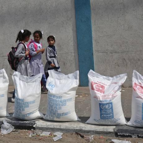 Meninas palestinas passam em frente a sacos de suprimentos da UNRWA, em Gaza Foto: SAID KHATIB / AFP