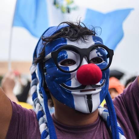 Um dos manifestantes pintou o rosto com as cores da bandeira da Guatemala e colocou um nariz vermelho, em referência a um palhaço, para protestar contra a corrupção no país Foto: JOHAN ORDONEZ / AFP