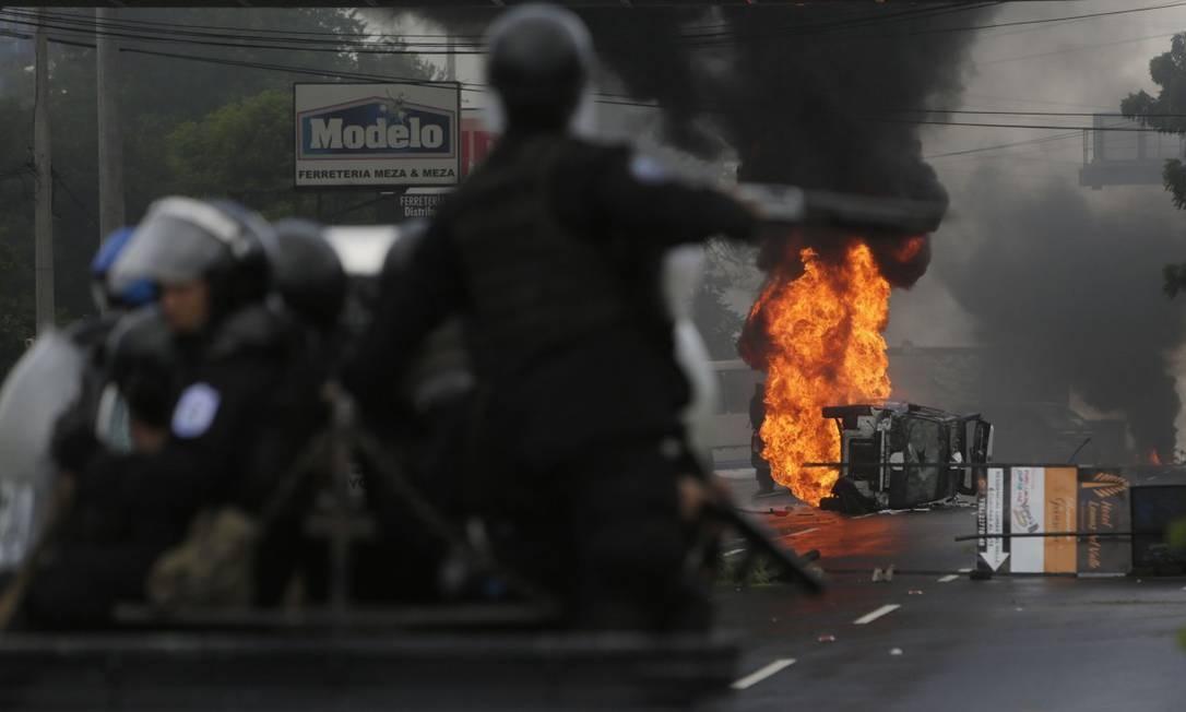 Membros do batalhão antichoque observam um carro da polícia incendiado após confronto com manifestantes em Manágua Foto: INTI OCON / AFP