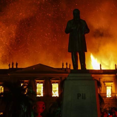 A estátua de D. Pedro II em frente ao Museu Nacional; atrás, a instituição em chamas Foto: Uanderson Fernandes / Agência O Globo
