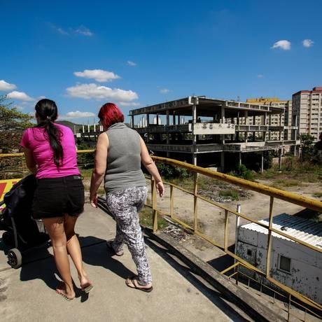 Mulheres atravessam passarela em frente a obras abandonadas de clínica e maternidade em São Gonçalo, no bairro do Colubandê Foto: Brenno Carvalho