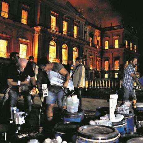 Voluntários e funcionários tentavam resgatar equipamentos de pesquisa enquanto o Museu Nacional ainda pegava fogo Foto: Ricardo Moraes/Reuters