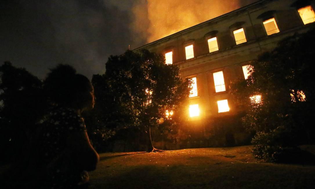 Mulher olha o prédio incendiado do museu, o mais antigo do Brasil, tendo este ano completado seu bicentenário Foto: Fabio Gonçalves / Agência O Globo