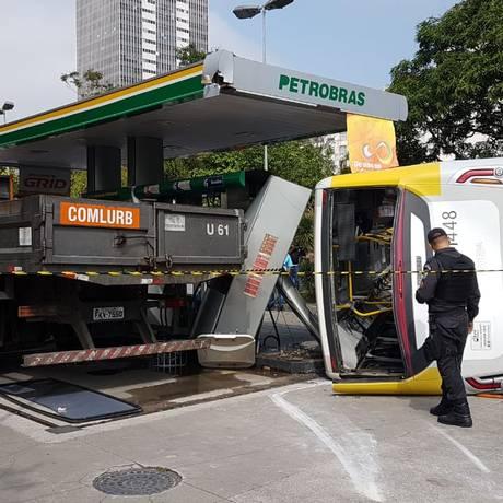 Um PM observa o ônibus tombado Foto: Brenno Carvalho / Agência O Globo