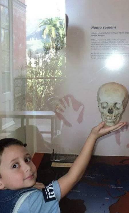 A brincadeira com um crânio virou parte da lembrança de Calebe Azevedo. A foto é de junho de 2012, e ele tinha apenas 3 anos. A imagem foi postada por Joana Azevedo em sua página no Facebook. Foram publicadas 24 fotos de momentos especiais do passeio, mas Joana lamentou não ter mais. Foto: Reprodução / Redes Sociais