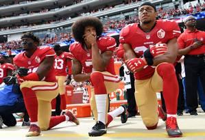 Colin Kaepernick (centro), ex-quaterback do San Francisco 49ers, se ajoelha em protesto à execução do hino nacional americano, em 2016 Foto: THEARON W. HENDERSON / AFP
