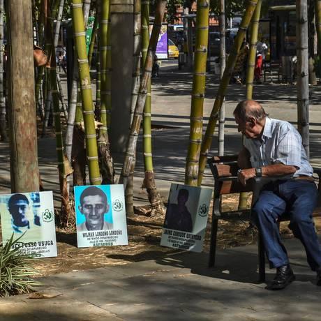 Homem observa fotos de desaparecidos em Medellin, Colômbia: guerrilha afirma que vai libertar prisioneiros por conta própria Foto: JOAQUIN SARMIENTO / AFP