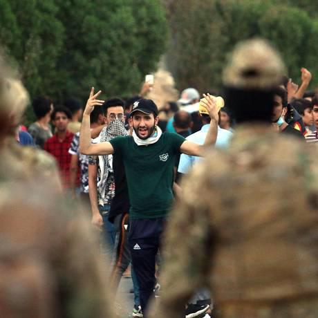 Manifestantes enfrentam forças de segurança do governo em protestos no sul do Iraque, em Basra Foto: HAIDAR MOHAMMED ALI / AFP