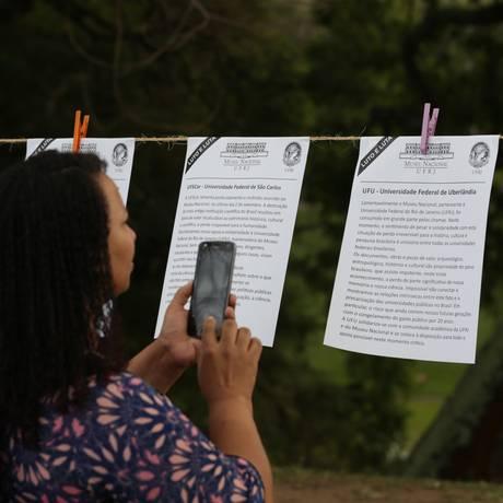 Mulher fotografa mensagens de outras universidades que lamentam incêndio no Museu Nacional Foto: Marcio Alves / Agência O Globo