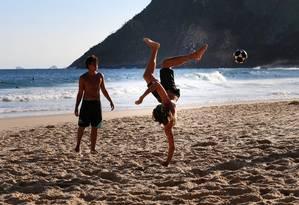 Técnica. Amigos treinam passes ousados de altinha na praia de Itacoatiara Foto: Roberto Moreyra / Roberto Moreyra