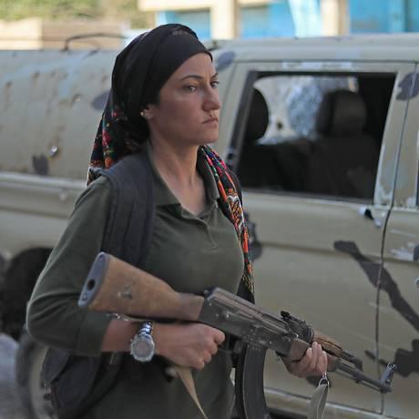 Uma combatente curda passa pela caminhonete do exército sírio envolvida no confronto Foto: DELIL SOULEIMAN / AFP
