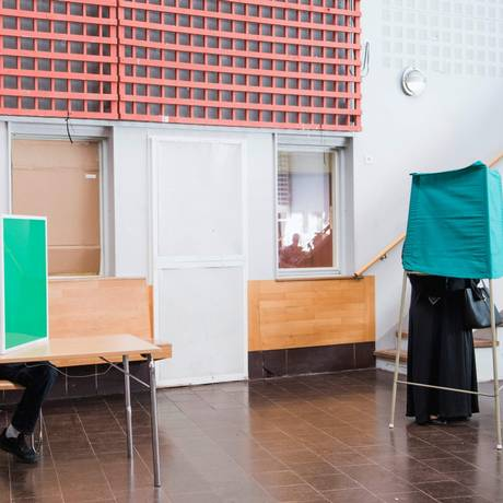 Eleitores suecos em cabines de votação neste domingo, em Estocolmo Foto: JONATHAN NACKSTRAND / AFP