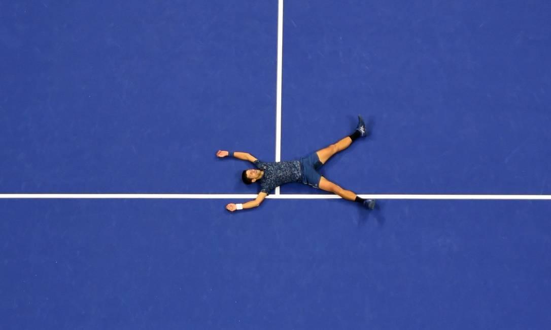 Novak Djokovic da Sérvia deita na quadra para comemorar sua vitória sobre Juan Martin del Potro da Argentina durante a partida de singles masculinos do Aberto dos EUA realizado em Nova York Foto: DON EMMERT / AFP