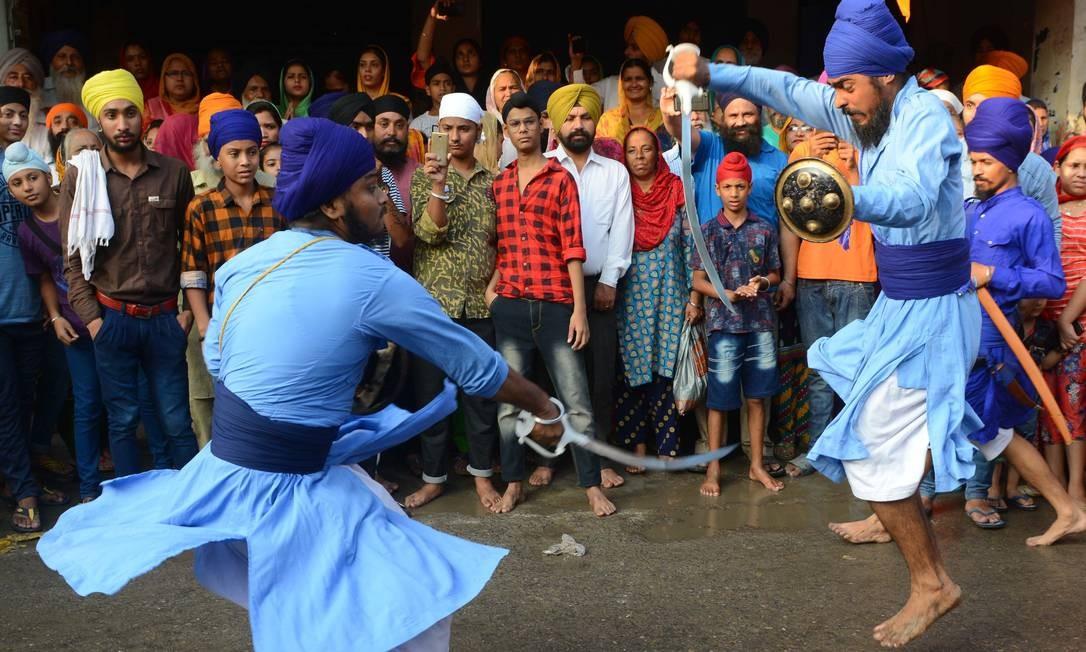 Jovens sikhs realizam a arte marcial conhecida como 'Gatka' durante uma procissão religiosa de Gurudwara Ramsar NARINDER NANU / AFP