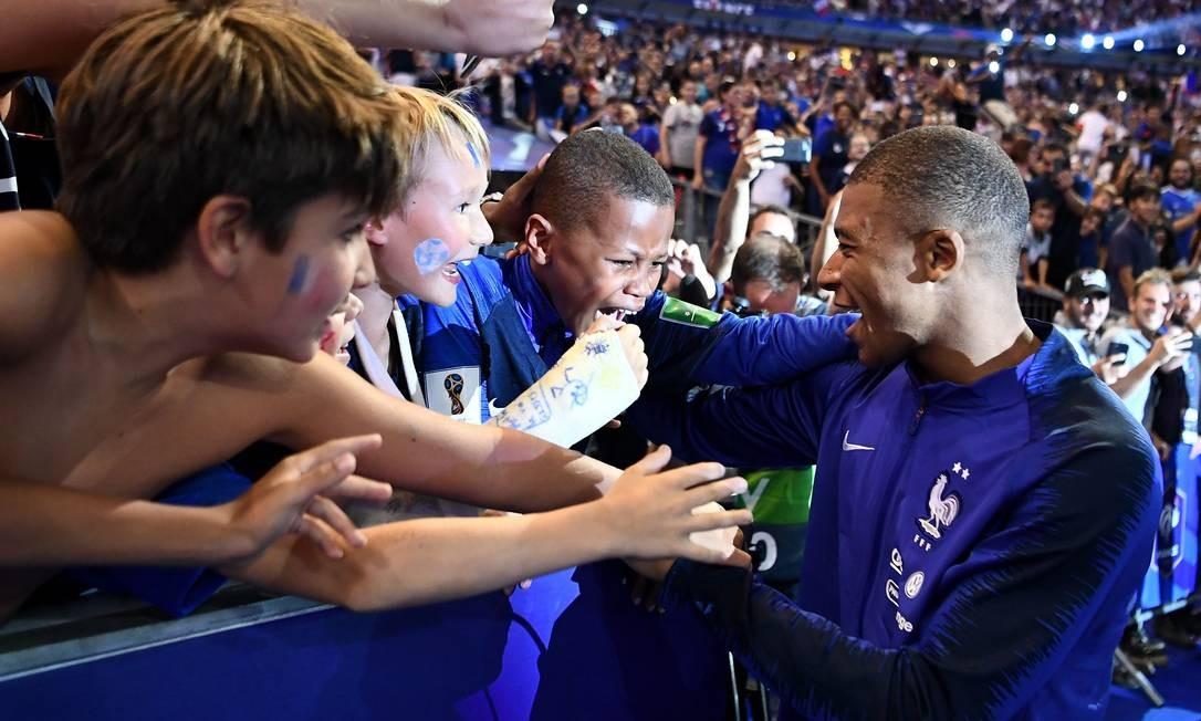 Um jovem torcedor chora ao se aproximar do seu ídolo o atacante da França Kylian Mbappe durante uma cerimônia para comemorar a vitória da Copa do Mundo de 2018. O Jogo no Stade de France foi contra a Holanda FRANCK FIFE / AFP