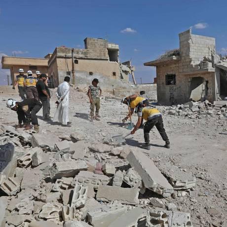 Equipes de resgate limpam escombros para abrir uma passagem em meio à destruição provocada por bombardeios do governo na cidade de Al Habit, na fronteira sul da província de Idlib, ocupada por rebeldes Foto: OMAR HAJ KADOUR / AFP