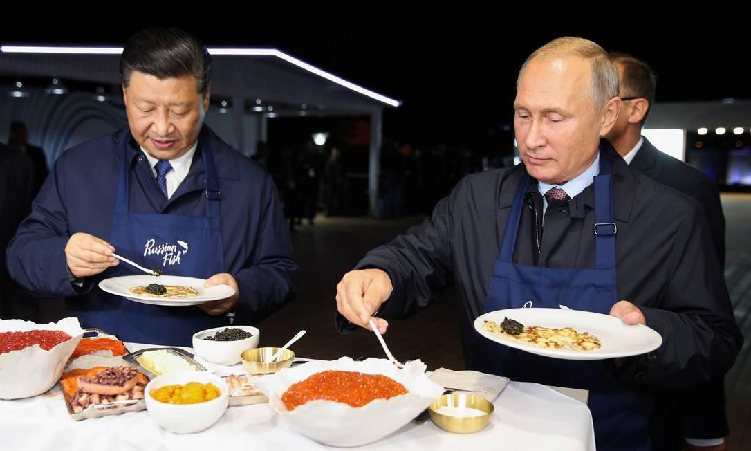 Xi Jinping e Vladimir Putin tomam café juntos no fórum em Vladivostok, de onde acompanham as manobras conjuntas Foto: POOL / REUTERS