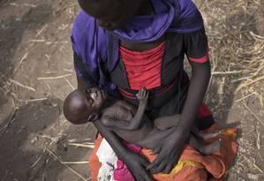 Imagem de arquivo mostra Adel Bol, de 20 anos, com a filha Akir Mayen, de apenas 10 meses, num centro de distribuição de alimentos no Sudão do Sul Foto: STR / AP