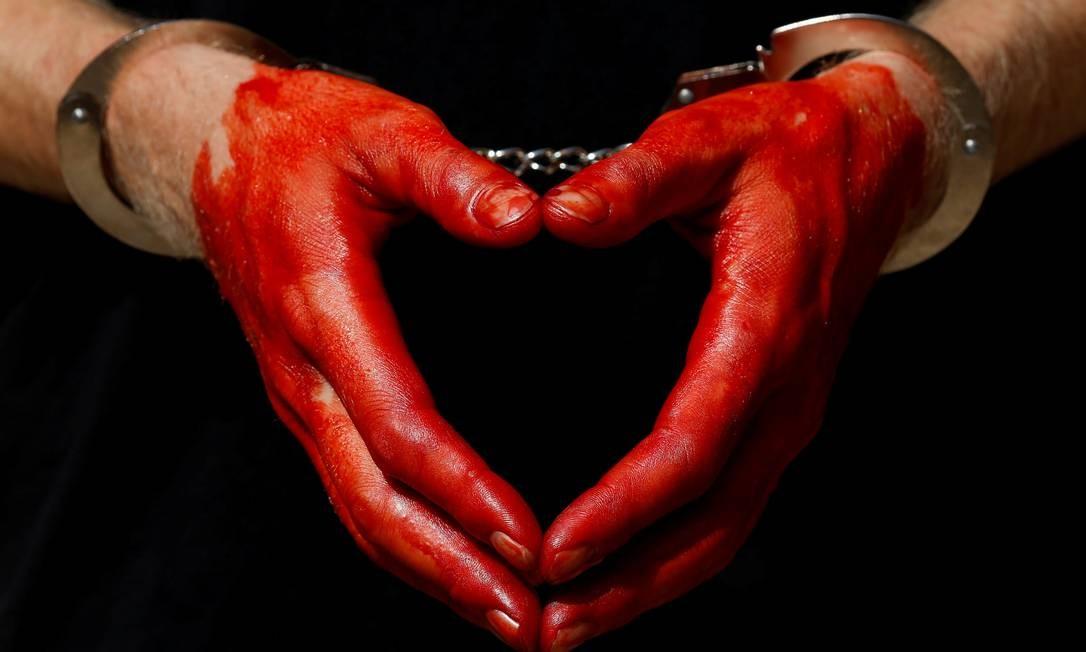 Um manifestante usa algemas nas mãos manchadas de sangue durante um protesto das ONGs humanitárias Lifeline e Sea-Watch em Valletta, Malta DARRIN ZAMMIT LUPI / REUTERS