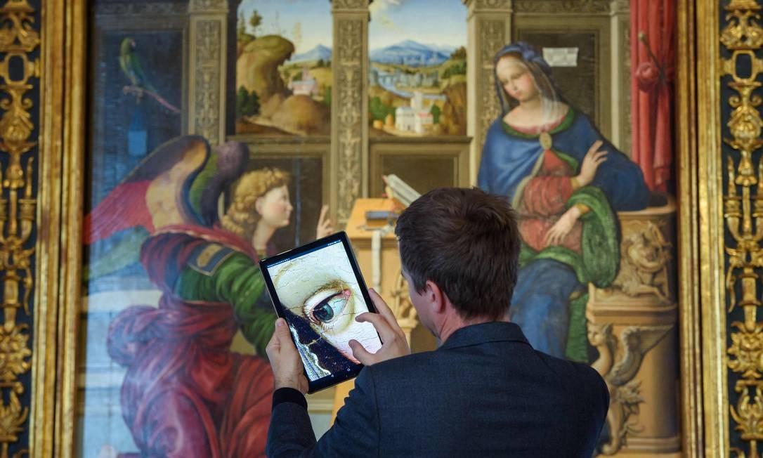 Um visitante usa um dispositivo móvel para ver um detalhe do trabalho de arte em uma fotografia de alta resolução exposta no museu Bode, em Berlim Foto: GREGOR FISCHER / AFP