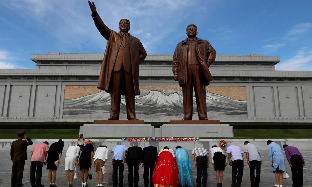 Um casal com suas famílias e amigos prestam homenagens diante das estátuas de bronze dos falecidos líderes Kim Il Sung e Kim Jong Il, antes de se casarem em Pyongyang, na Coréia do Norte Foto: DANISH SIDDIQUI / REUTERS
