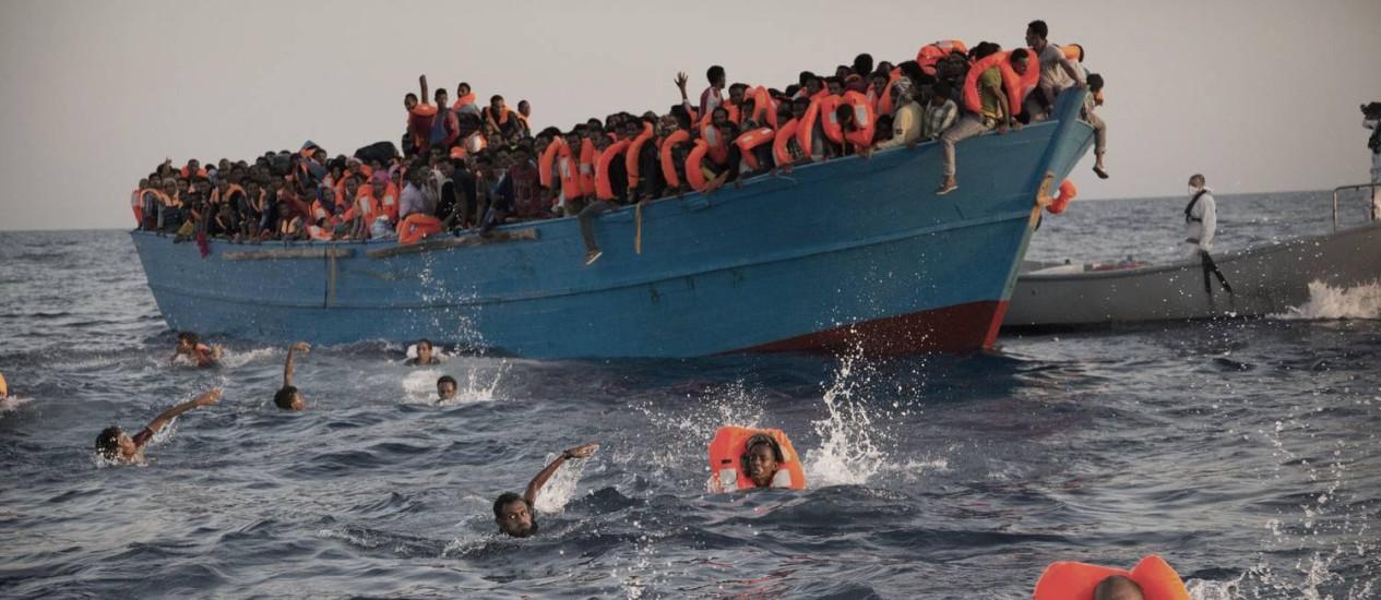 Migrantes nadam para barco de resgate, no Mediterrâneo, em agosto: crise migratória se agravou em 2015, mas rota entre Líbia e Itália tem se tornado mais mortal, proporcionalmente Foto: Emilio Morenatti / AP