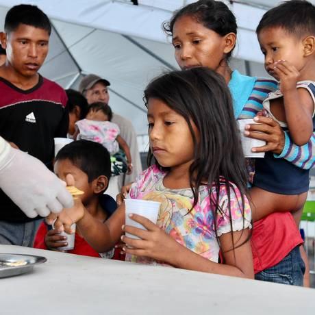 Venezuelanos recebem alimento em um centro de acolhimento em Paracaima, Roraima Foto: Ruy Baron / Agência O Globo