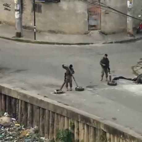 Policiais retiram barricadas de ruas da comunidade Foto: Reprodução/TV Globo
