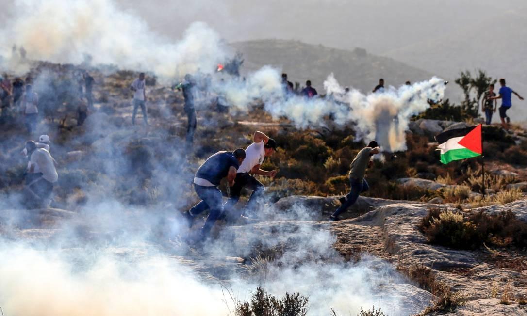 Linha de embate. Manifestantes palestinos fogem de gás lacrimogêneo disparado por forças israelenses na Cisjordânia em 4 de setembro de 2018; 60% do território é ocupado militarmente por Israel Foto: ABBAS MOMANI / AFP