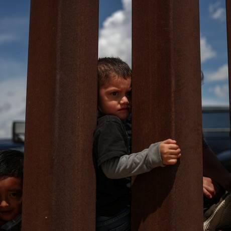 Crianças imigrante olha para fora do campo de detenção, enquanto aguarda após ser detida em tentativa de cruzar a fronteira Foto: ADREES LATIF / REUTERS
