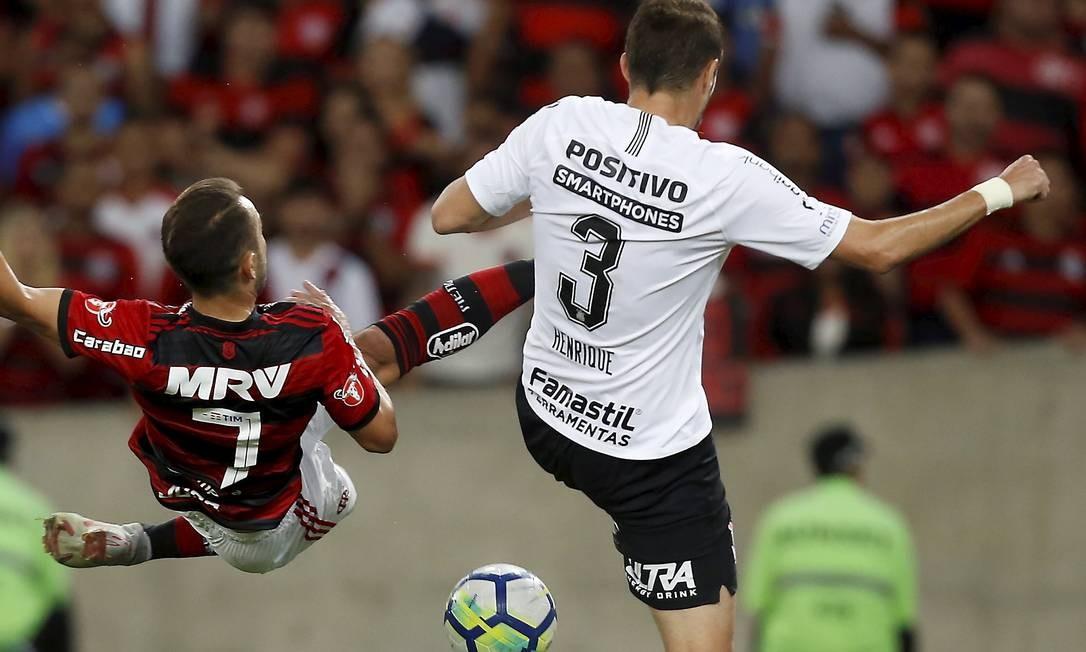 Marcado por Henrique, Everton Ribeiro tenta o voleio na partida contra o Corinthians Foto: MARCELO THEOBALD / MARCELO THEOBALD