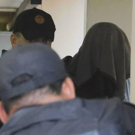 Com a cabeça coberta, policial é levado para penitenciária em Niterói Foto: Fabio Gonçalves / Agência O Globo