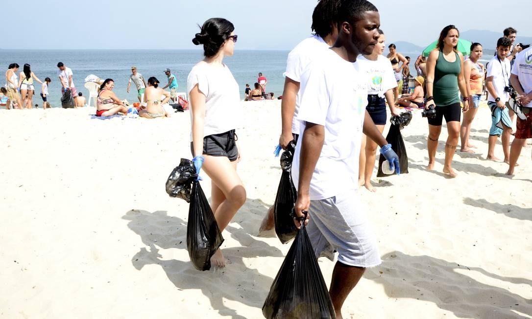 Consciência. Voluntários carregam sacolas com lixo recolhido na Praia de Icaraí durante a edição de 2017 do Dia Mundial da Limpeza de Rios e Praias Foto: Divulgação
