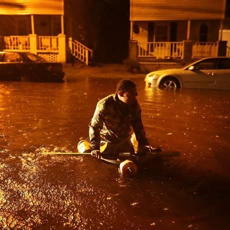 Homem atravessa rua inundada durante a passagem do furacão Florence em New Bern, na Carolina do Norte Foto: CHIP SOMODEVILLA / AFP