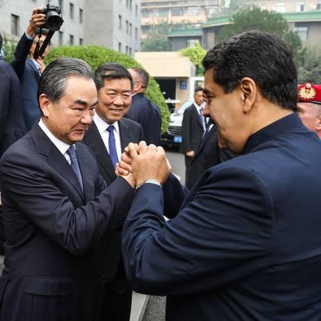 Maduro cumprimenta o chanceler chinês Wang Yi em Pequim Foto: MARCELO GARCIA / AFP