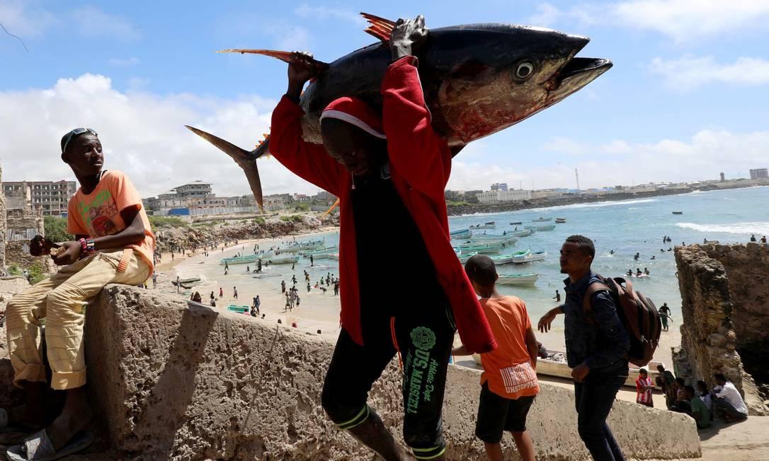 Um pescador leva sua captura perto de um porto de pesca em Mogadíscio, Somália FEISAL OMAR / REUTERS